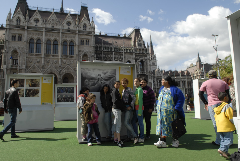 Models seeing a portrait from their village. Parliament Square, Budapest